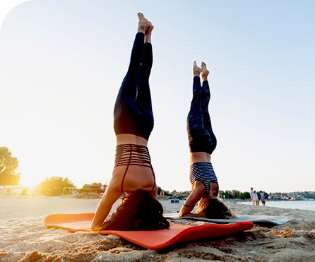 Two women do yoga on the beach