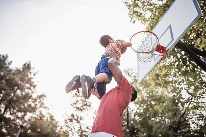 man painlessly hoists young son into air to dunk basket in basketball