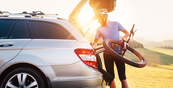 male cyclist loads bicycle into car as sun sets