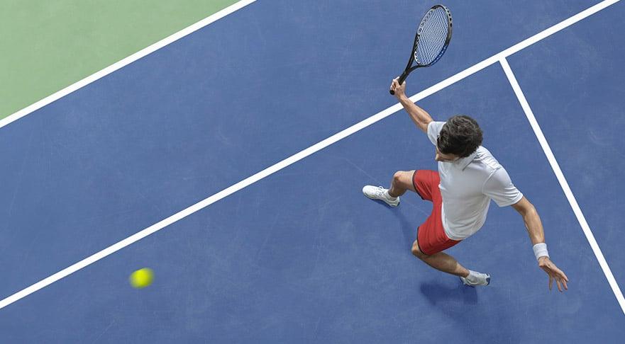 man makes tennis swing
